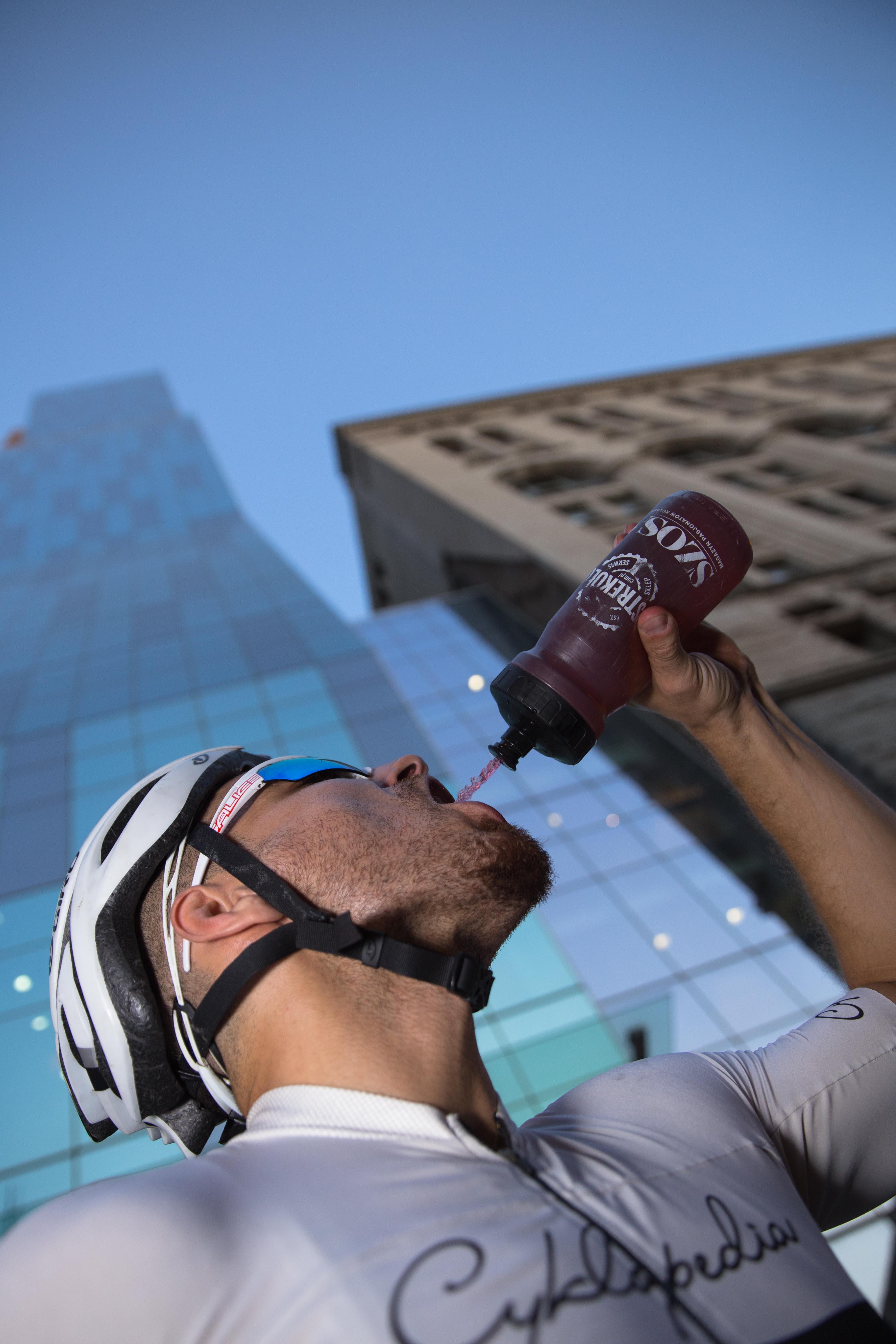 "Cyclist drinking from ""Ostre Kolo"" water bottle"