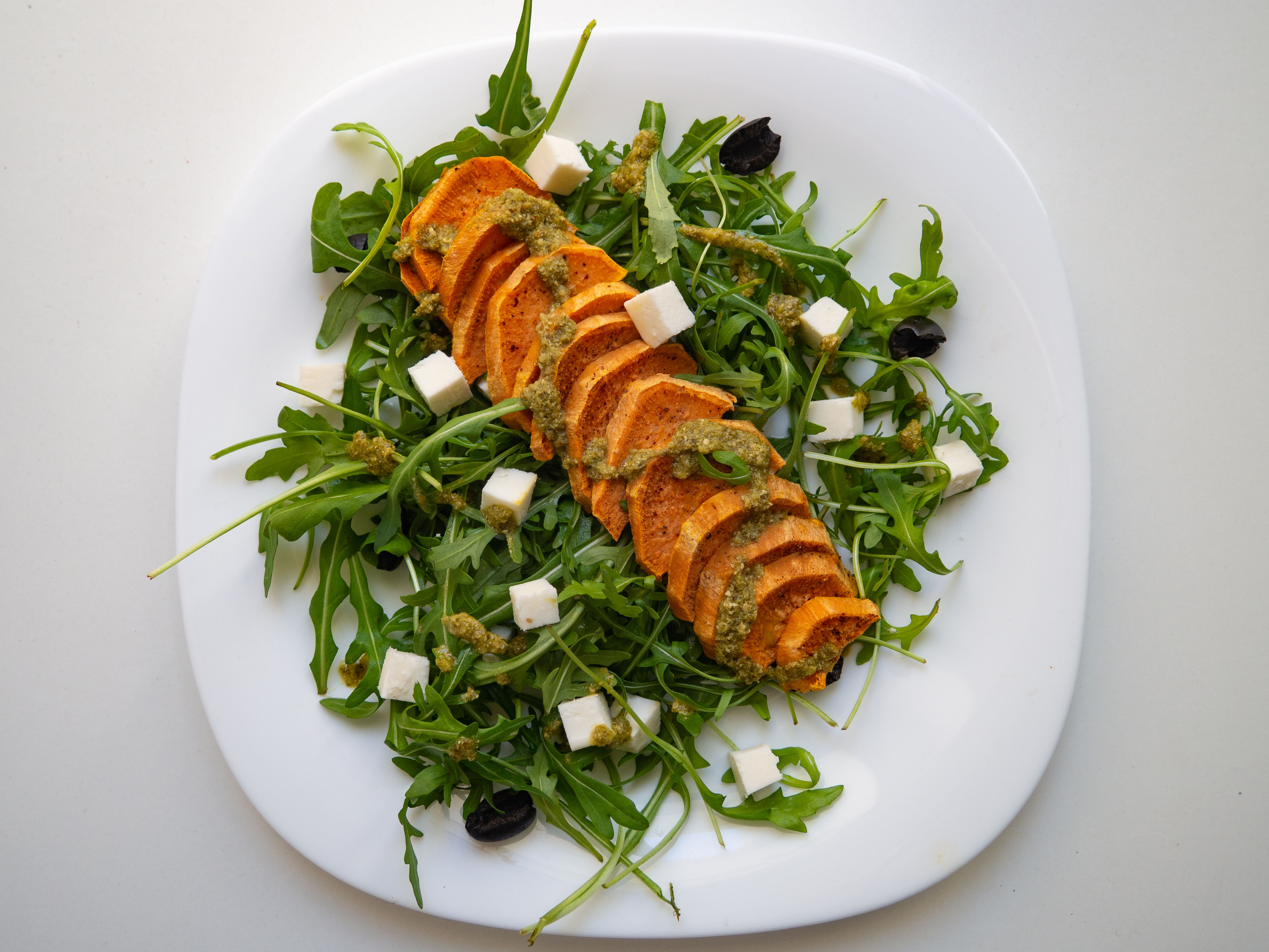 Sweet potatoes with feta cheese and pesto on rocket
